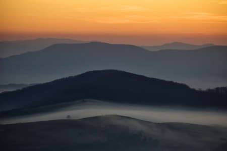 dark landscape with fog between hills and orange sky before sunrise
