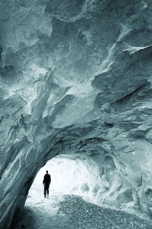 cavern: man walking out of a cold cave  Stock Photo
