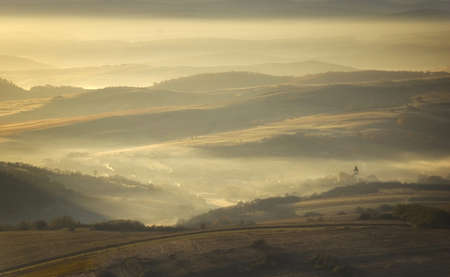 autumn morning with fog and sun rising over a mountain village Stock Photo - 13078482