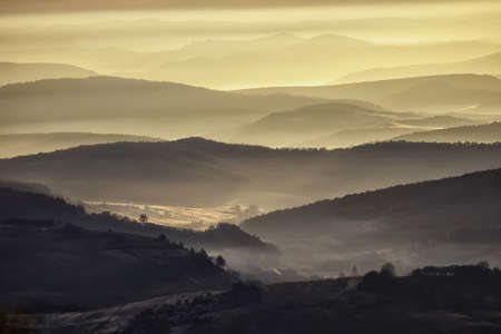 view of a valley in a beautiful early morning with fog between hills Stock Photo - 13840793