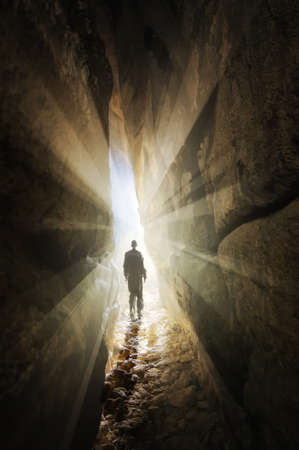 man walking out of a cave with rays