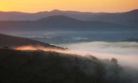 Autumn morning landscape with fog trough hills and first rays of sunlight photo