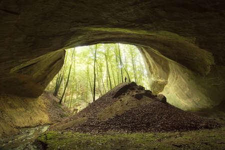 Cave entrance with man standing on top of hill Stock Photo - 18129391