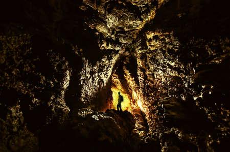 cueva: explorador en una cueva con la luz de oro en la oscuridad