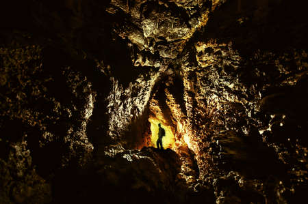 explorer in a cave with golden light in darkness Stock Photo - 18708469