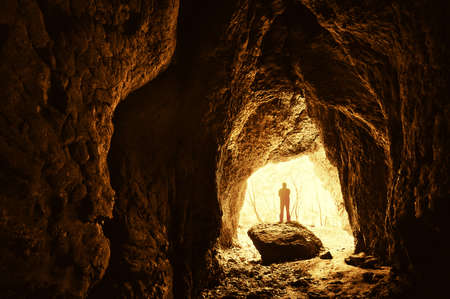 Cave with man standing on a rock in front of the entrance with trees behind him Stock Photo