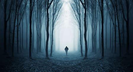 Man lopen in een donker bos met mist en bomen