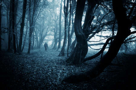 Mysterious scary man walking in a dark forest with fog and strange trees