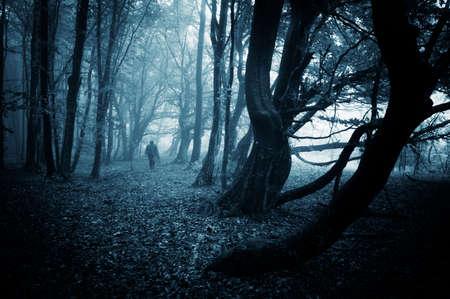 Mysterieuze enge man lopen in een donker bos met mist en vreemde bomen