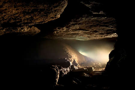 cave: Cave with light from speleologist