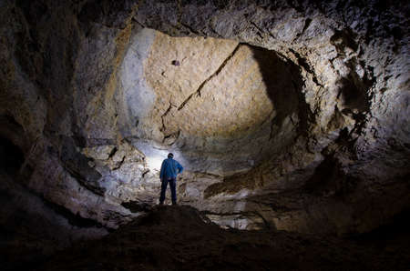 Man standing in a huge cave photo
