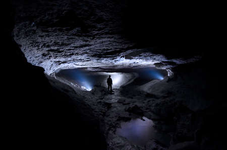 cave exploring: Cave with man exploring  Stock Photo