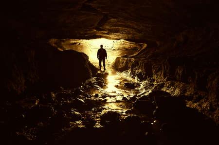 jaskinia: ciemnej jaskini z sylwetką człowieka i wody Zdjęcie Seryjne