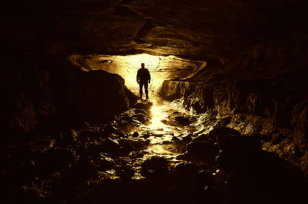 donkere grot met man silhouet en water
