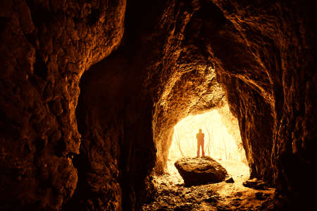 cave exploring: Cave with man standing on a rock in front of the entrance with trees behind him