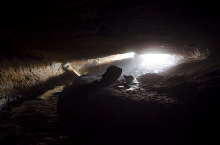 cave exploring: Cave entrance with ligh shining trough