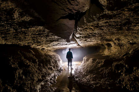 explorer man: Cave with man at entrance underground with light speleology