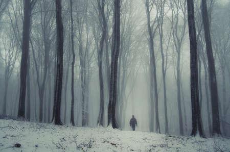 Man in bevroren bos met sneeuw in de winter