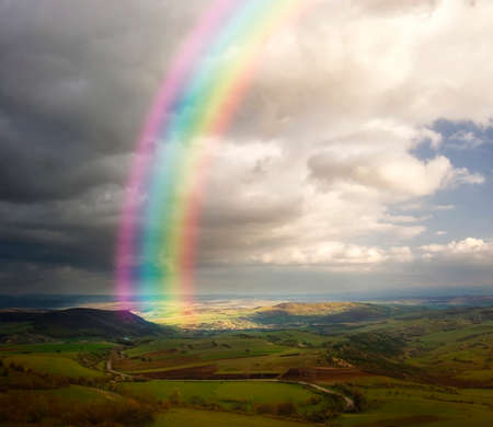 Rainbow over fields and meadows in spring with green grass and white clouds