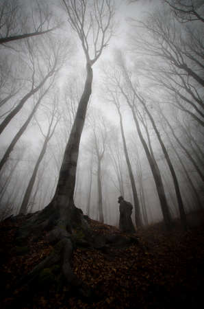 Vertical photo of scary man ghost near tree with big roots in dark mysterious haunted forest with fog on Halloween