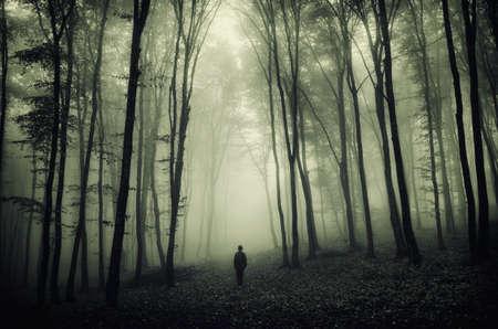Man in surrealistische bos met mist op Halloween