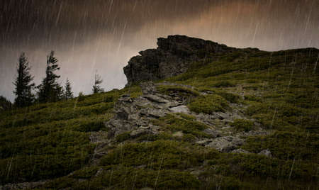 torrential: Rain falling over mountain cliffs and trees Stock Photo