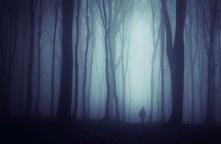 Man in geheimzinnig bos met mist op de nacht van Halloween