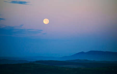 sky night: Moon rising over landscape with blue light Stock Photo