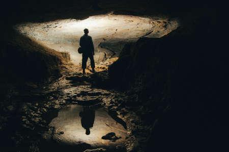 silueta hombre: Cueva de exploración con la silueta oscura del hombre