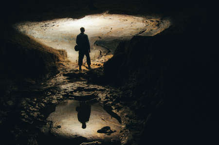 Cave exploration with dark silhouette of man Stockfoto