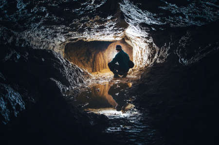 Underground cave with man exploring with light
