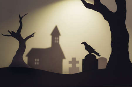 Halloween scene silhouettes with crow on tombstone n church graveyard Stock Photo
