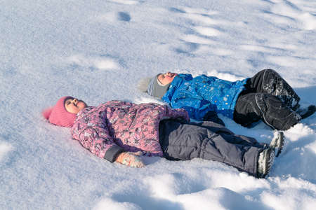 he   my sister: Children, brother and sister lying in the snow on the back. Laugh and smile. Dressed in jackets, hats, warm pants, boots, boots and mittens. Wear pink, blue, grey and black. He closed his eyes.