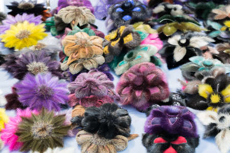 Several of the female pins in the form of fur flowers. The clips are on the table. Made of faux fur.