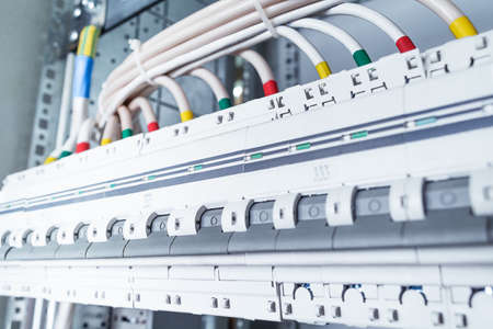 lugs: Connecting cables with cable lugs to circuit breakers in the electrical control panel on the artboard. Alignment of the components to ensure safety and reliability. Stock Photo