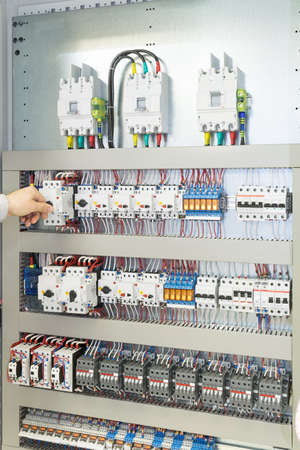 The man turns off the circuit breaker protecting the motor in an electric Cabinet or panel. Automatic switches connected by wires with marking. Top visible introductory circuit breaker. Stok Fotoğraf