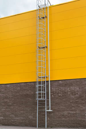 emergency stair: Metal staircase with railings on the roof on the Mall or the warehouse. Steel pipe to connect a fire hose to discharge the water to extinguish the roof. Stock Photo