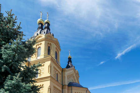 easter cross: On the background of blue sky with Cirrus clouds visible Orthodox Church yellow color with Golden domes. In the foreground is the pine or spruce green.
