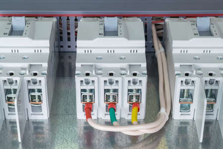 distribution board: On the mounting panel there are three power circuit breaker. To one circuit breaker connected wires with ferrules. Tips of red, green and yellow. Stock Photo