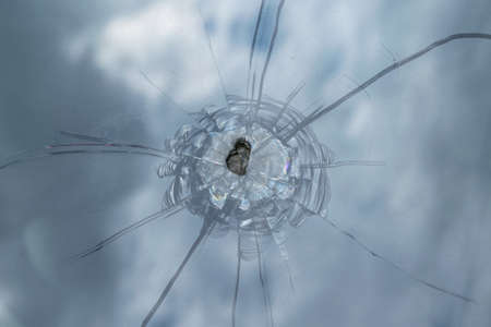 The broken windshield of the car from flying stone. The hole in the glass, chips and debris, cracks in strips. The glass reflects the sky with clouds.