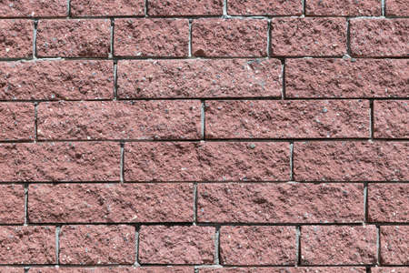 solid background: The wall and the bricks are red or brown. Masonry of bricks laid horizontally. The joints between the bricks with cement. Stock Photo