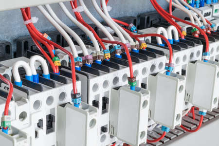 distribution board: The number of contactors arranged in a row in an electrical closet. The contactors connected wire number coded. Contactors with front auxiliary contacts. The wires go into perforated cable channels.