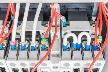 lugs: Several contactors are mounted on mounting panel. To them attached to an electrical wire lugs and number coded. Two wires are connected by a semicircle.Professional Assembly electric rack. Stock Photo
