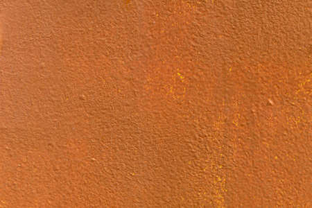 hollows: The metal walls are painted orange and yellow paint. The painted surface rough with small cracks and stains. Texture with many bumps and hollows.
