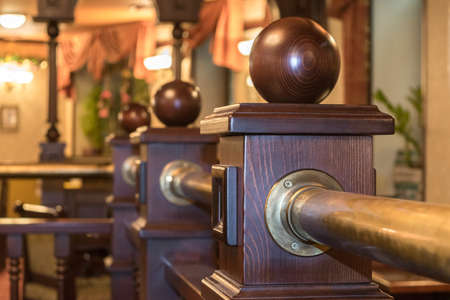 caoba: A fragment of a wooden fence in the interior of the restaurant or cafe. The fence posts with wooden balls. In the background is a cozy and comfortable interior with lamps and curtains.