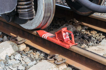 Railway brake Shoe or for keeps on the rails of the railway car. Iron wheels with shock absorbers or suspension springs. Metal rails with concrete sleepers. The brake is painted with red paint.