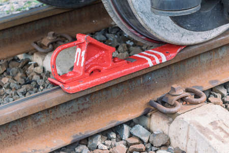 Train Shoe locks or keeps on the rails of the wagon. The metal wheels. Metal rails with concrete sleepers. Brake painted in red paint with white stripes.