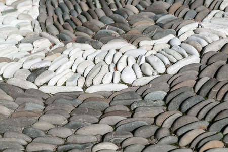autumn colour: White oval stones stacked arch or semi-circle among the dark stones. The stones are located one behind the other in several rows. Between the stones are small leaves.