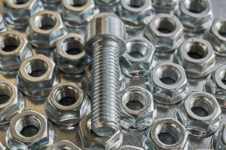 The threaded bolt lies on the shiny hex nuts. Nuts lie in several rows on a metal panel for electrical Cabinet. The nuts round base. Fasteners to building structures.