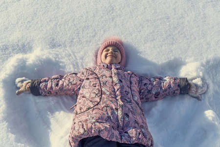 Girl lying on her back in the snow, hand in hand. The girl narrowed her eyes and wrinkled my nose and smiles. She was pleased and happy. Tracks in the snow from his hands like the wings of an angel.